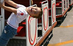 Little happy boy playing and hanging on the side of sightseeing. Train Stock Image