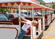 Little happy boy playing and hanging on the side of sightseeing. Train Royalty Free Stock Image