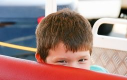 Little happy boy playing hide and seek on sightseeing train seat. S Royalty Free Stock Photography