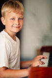 Little happy boy plays piano Stock Images