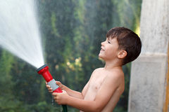Little happy boy pours water outdoor Stock Photography