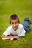 Little happy boy reading book Stock Photos