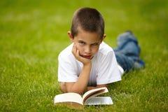 Little happy boy reading book Stock Photo