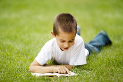 Little happy boy reads book lying on grass Stock Photo