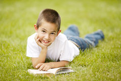 Little happy boy reads book lying on grass Stock Images