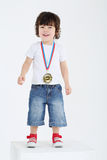 Little happy boy in red sneakers stands on large white cube Stock Photo