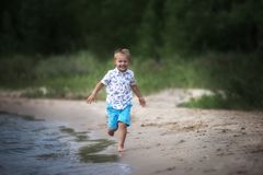 Little happy boy is running on the beach stock images