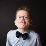 Little happy boy showing his tongue. Against the black Stock Photography
