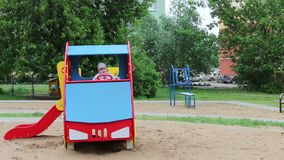 Little happy boy sits in colored wooden car at playground stock video