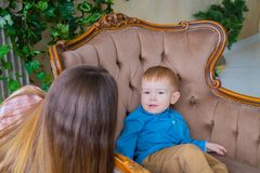 Little happy boy sitting on the chair royalty free stock photo