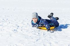 Little boy on a winter walk. Little happy boy sliding from the snowy hill down Royalty Free Stock Photos