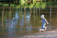 Little happy boy smiles and goes in water of pond Royalty Free Stock Images