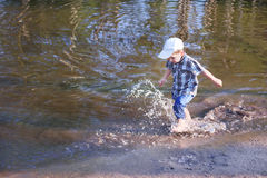 Little happy boy smiles and runs in water of pond Royalty Free Stock Photos