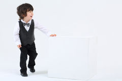 Little happy boy stands near large cube and laughs on white back Stock Images