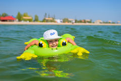 Little happy boy swimming at sea with rubber ring. Stock Images