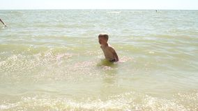 Little happy boy swimming in the sea and splashing water. Slow motion. Little happy boy swimming in the sea and splashing water. The child is resting and having stock video