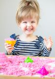 Little Happy Caucasian Girl Playing with Pink Kinetic Sand at Home stock images