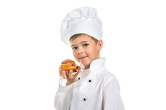 Little happy chef holding delicious tasty raisin bun with a golden crust Stock Image