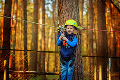 Little happy child boy in adventure park in safety equipment in summer day. Royalty Free Stock Photos