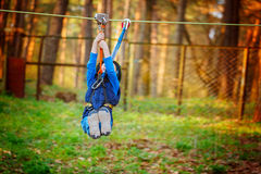 Little happy child boy in adventure park in safety equipment in summer day. Stock Images