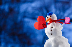 Little happy christmas snowman heart love symbol outdoor. Winter season. Little happy christmas snowman in blue screw top as hat red scarf and with heart love Royalty Free Stock Photos