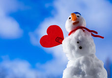 Little happy christmas snowman red heart love symbol outdoor. Winter. Little happy christmas snowman in blue screw top as hat red scarf and with clip red heart Royalty Free Stock Photo