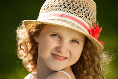 Little happy curly girl in a hat Stock Photos
