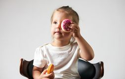 Little happy cute girl is eating donut stock photo