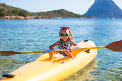Little happy cute girl enjoy kayaking in the clear Stock Image