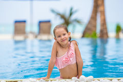 Little happy cute girl in outdoor swimming pool Stock Images