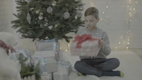 Little happy excited boy opening christmas present gift box in decorated new year tree festive atmosphere room stock video