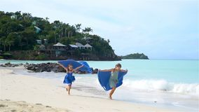 Little happy funny girls have a lot of fun at tropical beach playing together. Little girls having fun at tropical beach playing together. Adorable little stock video footage