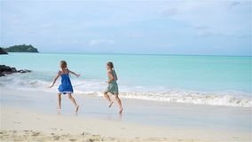 Little happy funny girls have a lot of fun at tropical beach playing together. SLOW MOTION. Little girls having fun at tropical beach playing together at shallow stock footage