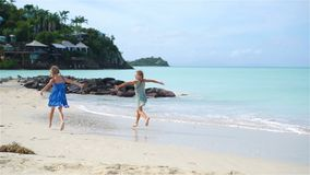 Little happy funny girls have a lot of fun at tropical beach playing together. SLOW MOTION. Little girls having fun at tropical beach playing together at shallow stock video footage