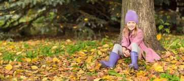 Little happy girl in autumn park outdoors royalty free stock photography