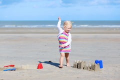 Little happy girl building sand castles on the beach Royalty Free Stock Photos