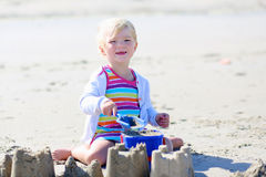 Little happy girl building sand castles on the beach Royalty Free Stock Photo