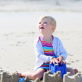Little happy girl building sand castles on the beach Stock Photography