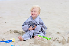 Little happy girl building sand castles on the beach Royalty Free Stock Images