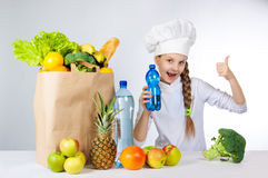 Little happy girl in a cap cook a variety of fresh food. A girl holding a bottle of pure mineral water for cooking healthy meals. A girl holds a finger up Royalty Free Stock Photography