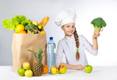 Little happy girl in a cap cook a variety of fresh food. Girl holding broccoli. and shows OK. Positive human emotion, facial expre. Ssion feeling, attitude. Bag Stock Images