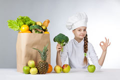 Little happy girl in a cap cook a variety of fresh food. Girl holding broccoli. and shows OK. Positive human emotion, facial expre. Ssion feeling, attitude. Bag Stock Image