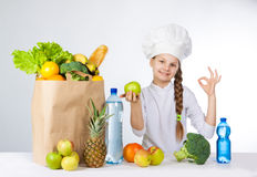 Little happy girl in a cap cook a variety of fresh food. Girl holding a green apple. and shows OK. Positive human emotion, facial Royalty Free Stock Photo