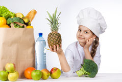 Little happy girl in a cap cook a variety of fresh food. Girl holding pineapple. and shows OK. Positive human emotion, facial expr Stock Photography