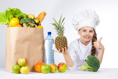 Little happy girl in a cap cook a variety of fresh food. Girl holding pineapple. and shows OK. Positive human emotion, facial expr. Ession feeling, attitude. Bag Stock Images