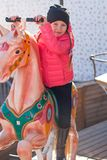 Little happy girl on carousel at an amusement park Royalty Free Stock Image