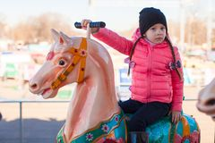 Little happy girl on carousel at an amusement park Stock Images
