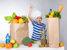Little happy girl in chef hat with big bags of products held up her hand and showing thumbs up V Stock Images