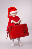 Little happy girl with christmas suitcase Royalty Free Stock Photos