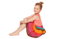 Little happy girl in colorful skirt sits, isolated on white background Royalty Free Stock Photo